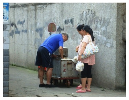 People buy steamed buns from street in China.